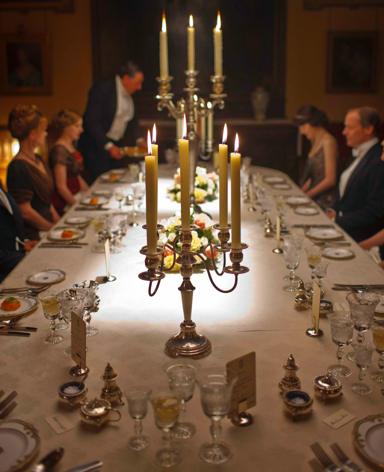 table is set at downton abbey with full service layed out, lit candles and guests dressed up.