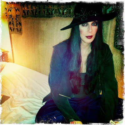 Cher tops the look with a black hat