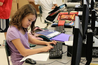 A young girl sits at a computer, gaze focused on a sheet of notebook paper and fingers poised on the keyboard.