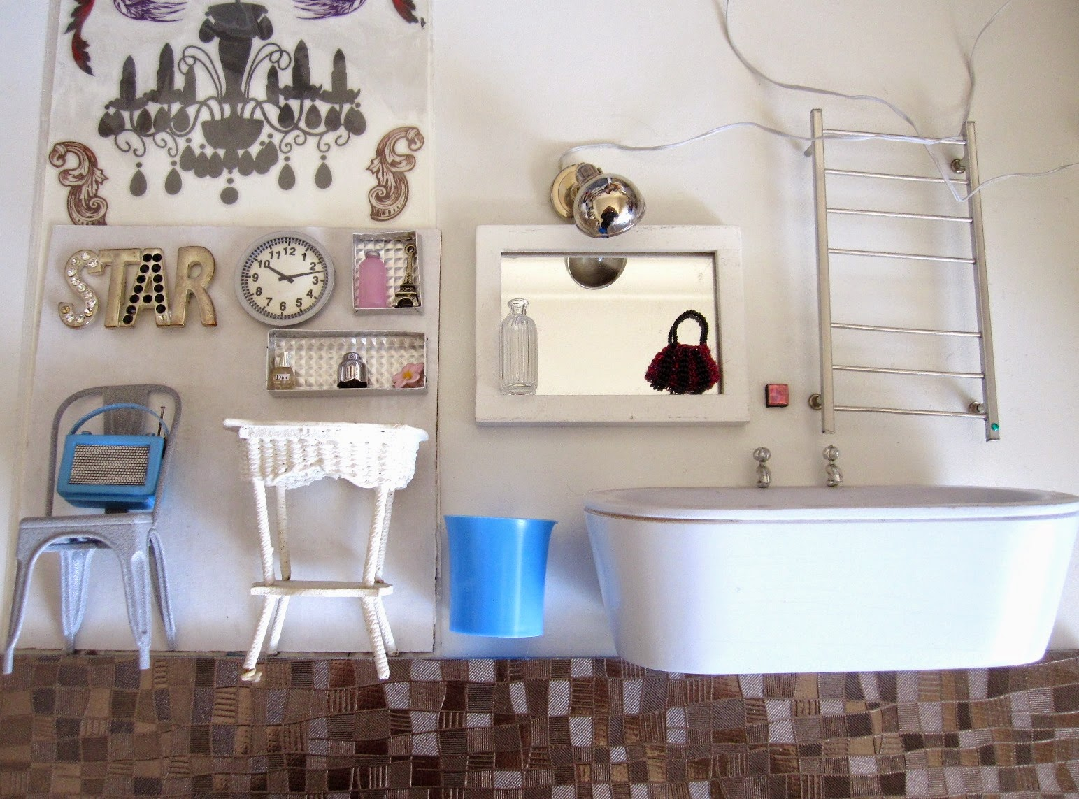 Selection of silver and white dolls house bathroom miniature furniture and accessories, with a full-sized silver-coloured placemat used as flooring and a range of silver, pink, white and blue miniature accessories.