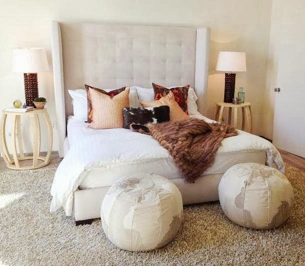 Master bedroom with wingback headboard and leather poufs