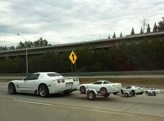 A Corvette towing a corvette shaped trailer towing a smaller covette shaped trailer towning a smaller yet corvette shaped trailer.