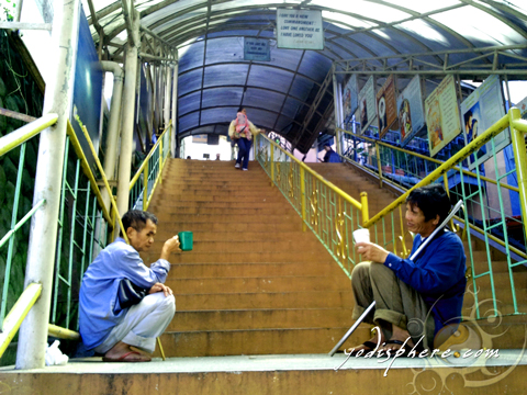 Two beggars sitting at the stairs going to the church