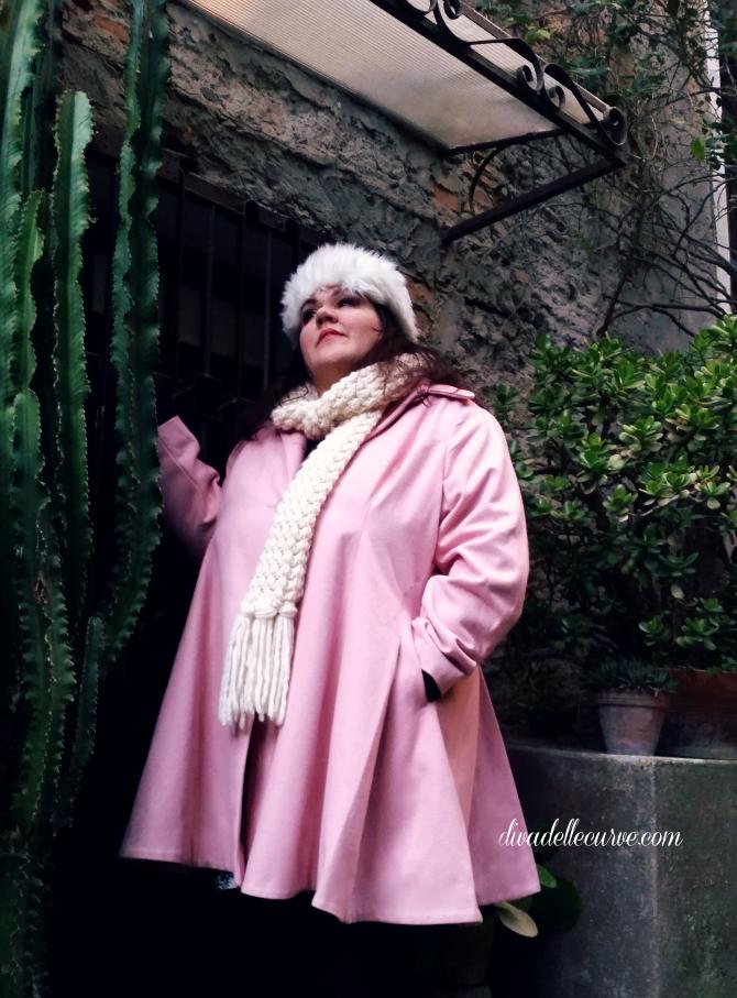 outfit taglie comode con cappotto rosa svasato nel giardino mediterraneo