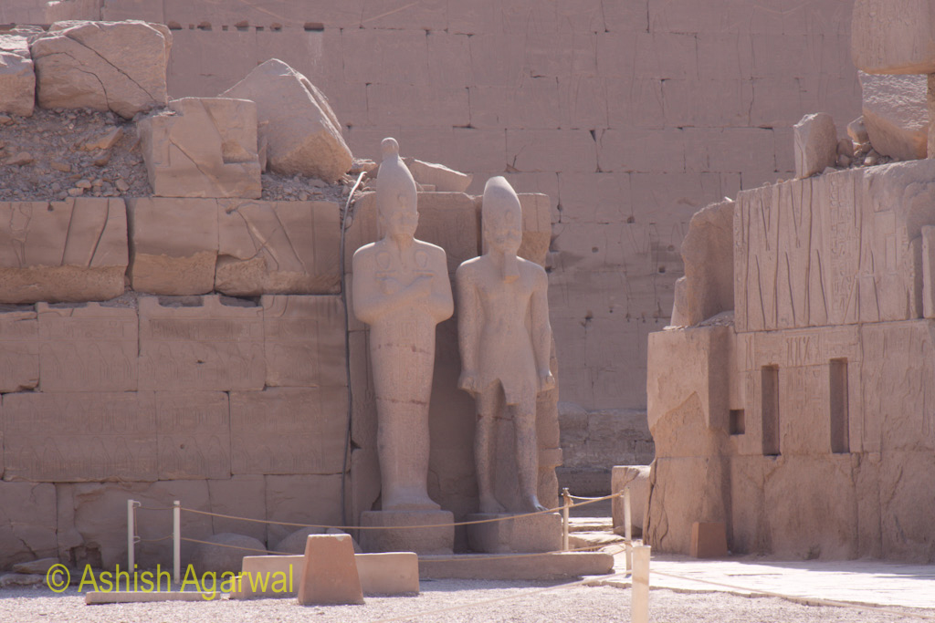 A couple of large statues against a wall inside the Karnak temple in Luxor