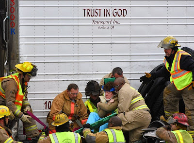 truck labeled Trust In God Transportation crushes woman against barrier