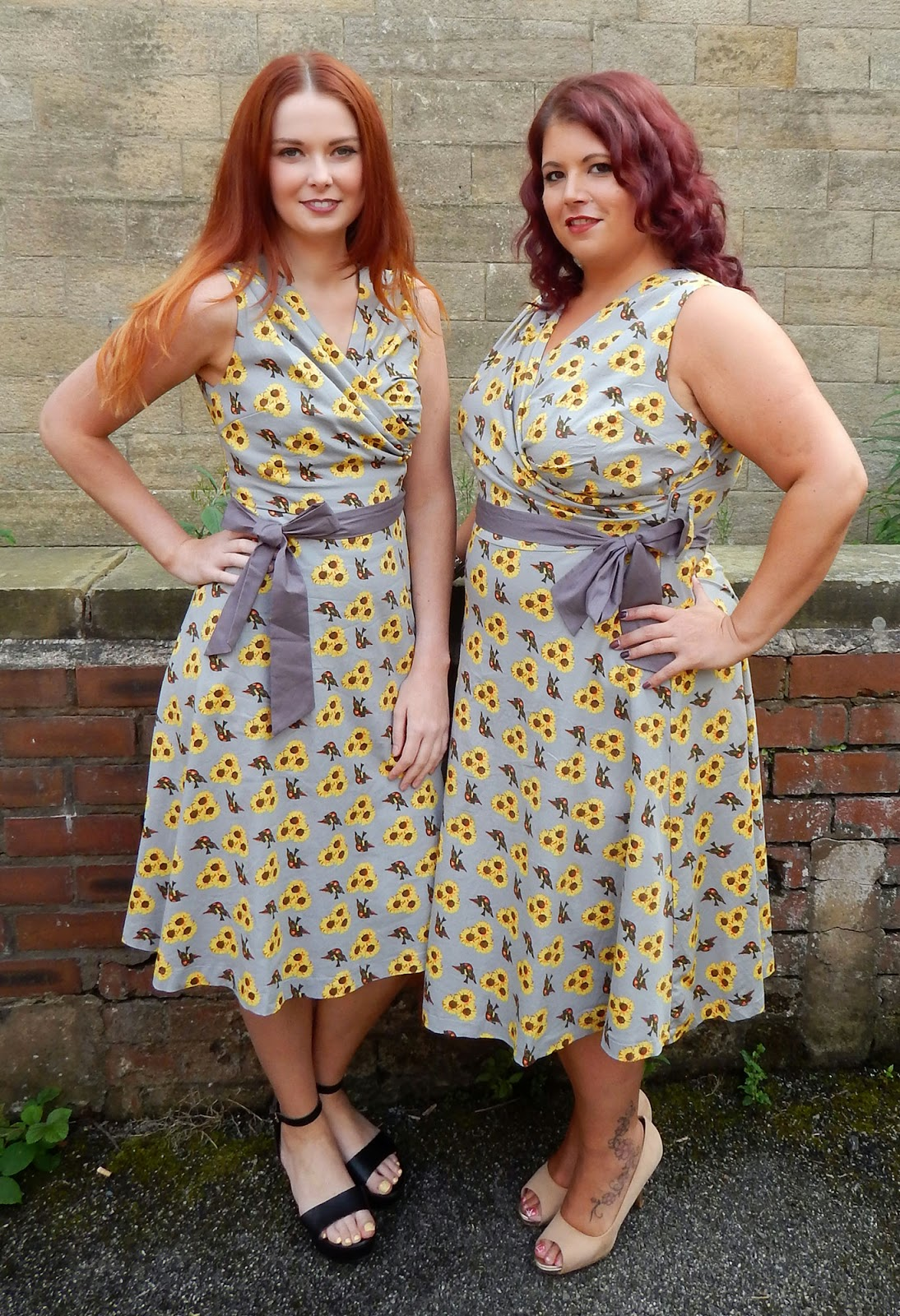 Grey sunflower print 1950's style dresses on two models