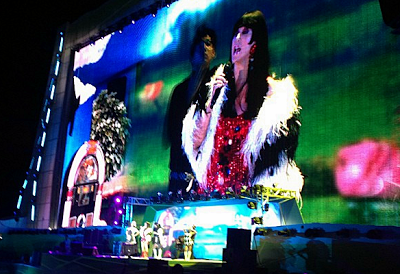 Cher singing in a 1960's style outfit