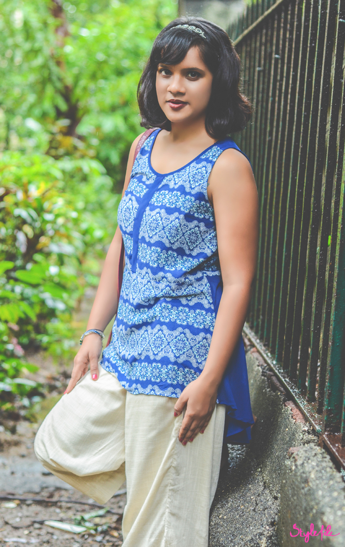 Wearing a Liva infused sheer blue printed tunic and cream culottes, Dayle Pereira of Style File India styles her personal style outfit with a Forever 21 burgundy sling bag, clogs, an embellished hairband and dark lips on a background of greenery in the monsoons as it rains