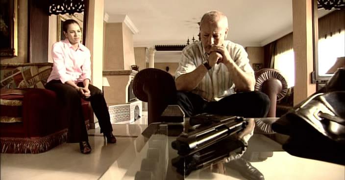 fotograma de la pareja protagonista en el salón con una pistola en la mesa.  imagen con tonos cálidos