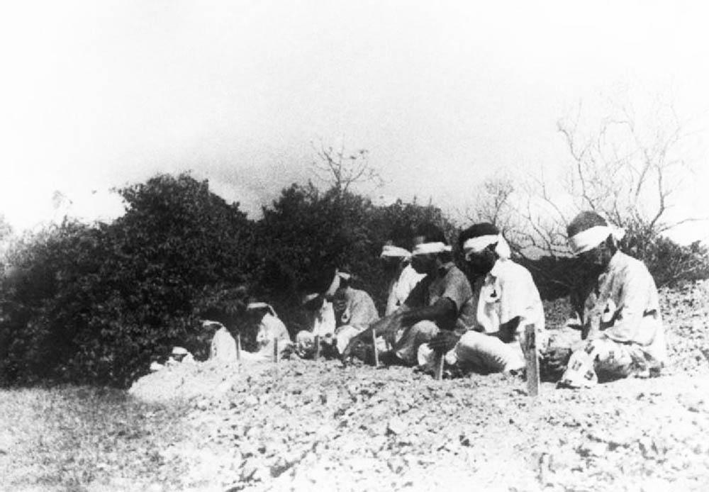 Sikh prisoners sitting in the traditional cross legged prayer position.