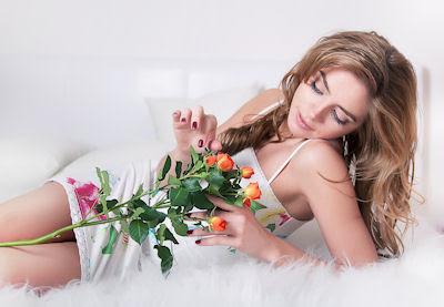 Mujer sexy y muy hermosa mirando sus lindas rosas