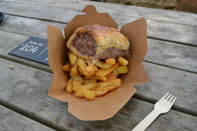 A large sausage roll on top of a pile of chips