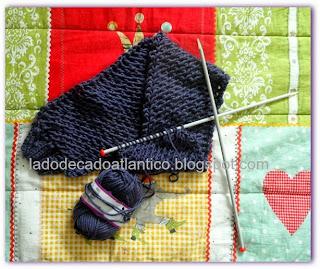 Imagem de um cachecol de tricô em ponto ajurado, com duas agulhas de tricô e um novelo.