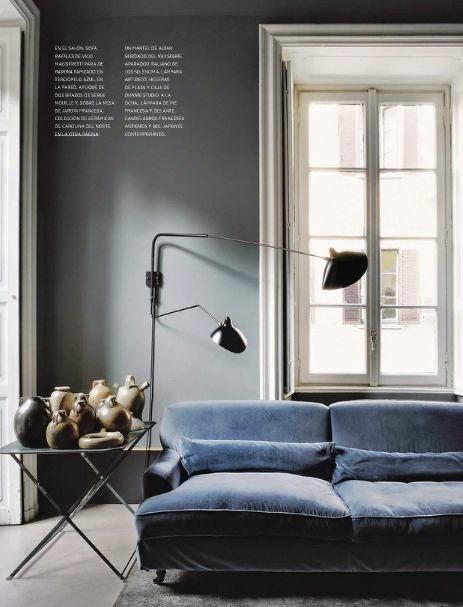 Sofa w kolorze niebieskim i dzbanki na stoliku obok