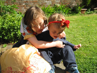 Two children cuddling in a garden