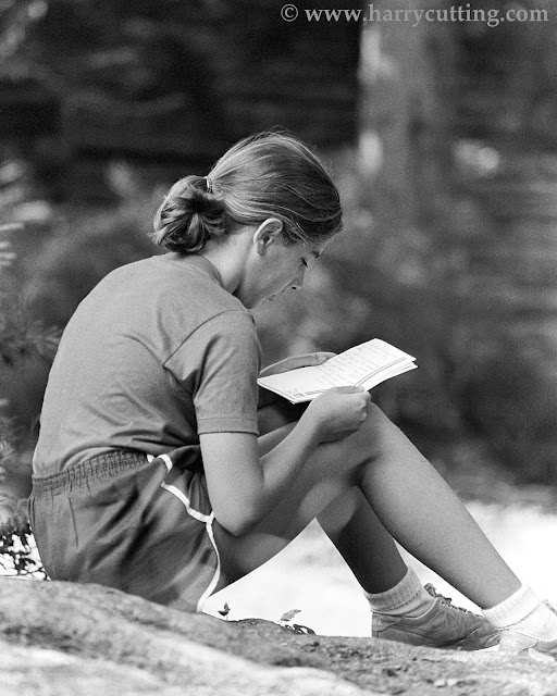 Young girl, sitting in the woods, reads letter from home at summer horseback riding camp in Vermont.