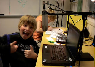 Boy giving a thumbs up sitting by a computer.