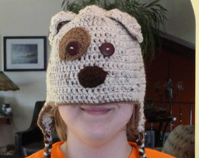 woman wearing crocheted dug hat over face