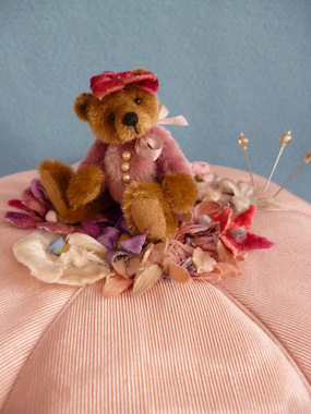 Harriet is sitting on a pin cushion trimmed with vinatge flowers.