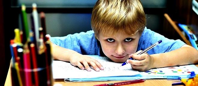 Menino aparentando ter 7 anos escrevendo com a mão direita sobre uma carteira escolar