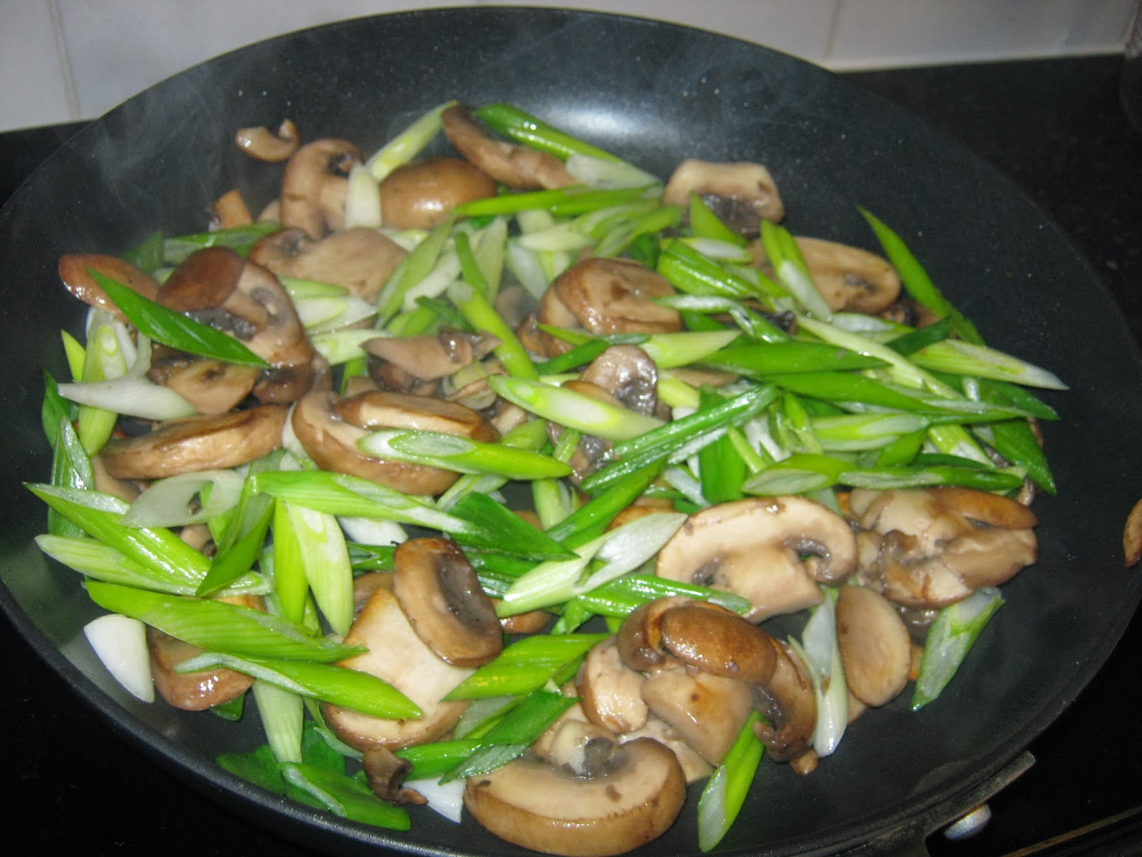 Mushrooms and spring onions being fried