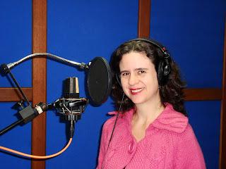 Fotografia de Letícia Schwartz em um estúdio de gravação. Ela está em frente a um microfone de pedestal e usa fones de ouvido. Sorri para a câmera.