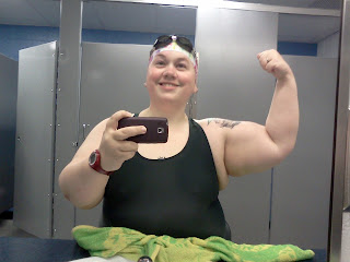 Post-swim self-photo in my swimsuit, cap, & goggles flexing my bicep