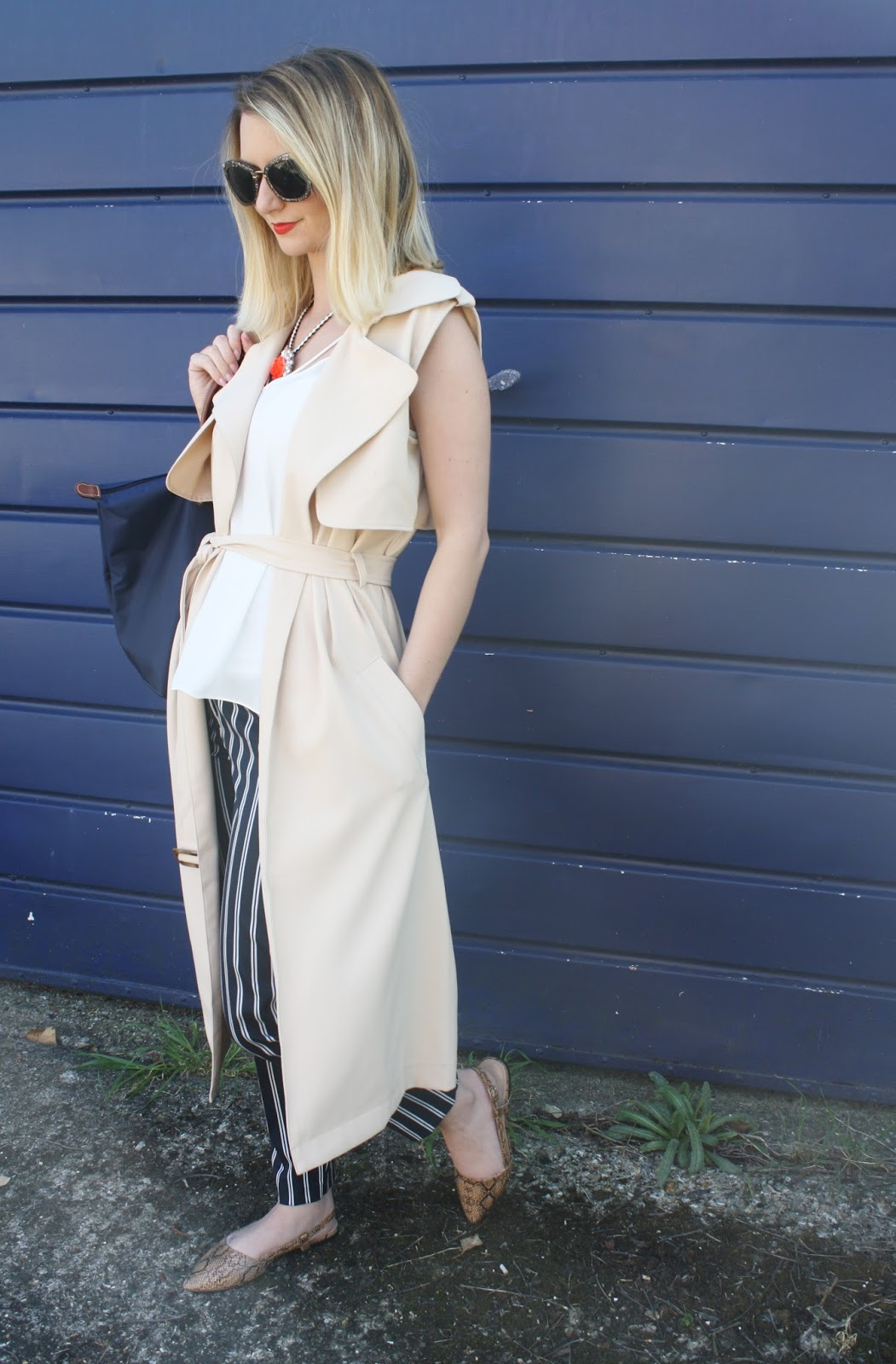 camel sleeveless trench styled with navy trousers and bag