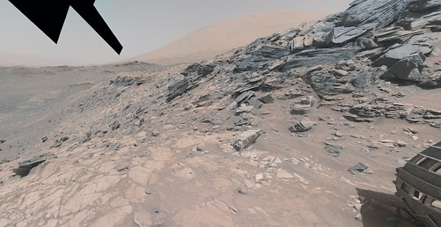 View from Marias Pass in Gale crater, Mars, where scientists found high concentrations of silica in the light toned bedrock seen in the lower half of the image. The Buckskin drill hole where the mineral tridymite was detected is visible in the lower left part of the image. Mount Sharp (Aolis Mons), the mountain in the center of Gale Crater is seen in the background, and the right front wheel of the Curiosity rover is seen to the right in the image. The image is made up of a number of smaller images by Curiosity's arm-mounted camera. (Photo credit: NASA/JPL-Caltech/MSSS)