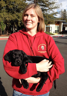 Gina (wearing a red sweatshirt) smiles holding a young black Lab puppy in her arms.