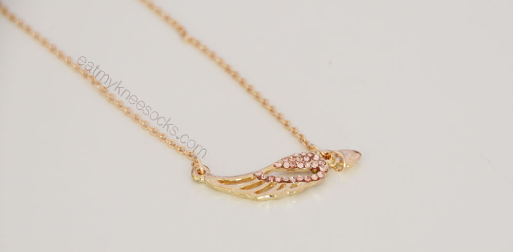 The golden wing necklace from Born Pretty Store features cutouts, rhinestones, and a dangling heart.