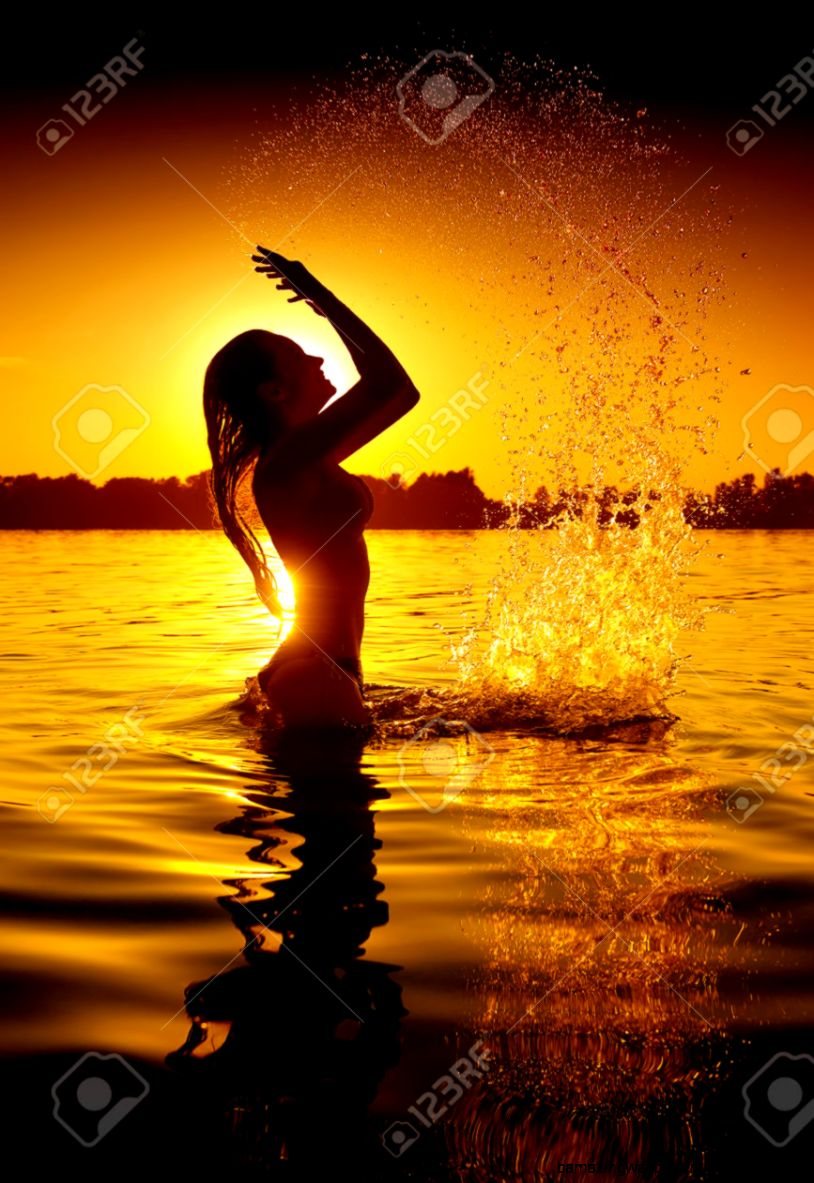 Teen Girl Swimming And Splashing On Summer Beach Over Sunset Stock