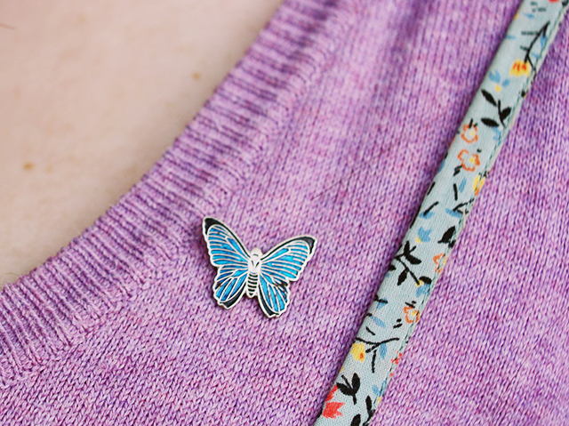 butterfly brooch on lilac top and flower dress