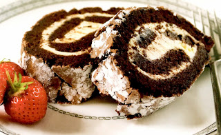 Two chocolate roulade slices filled with cream served garnished with strawberries