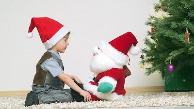 Un niño platica con Santa Claus junto al árbol de Navidad