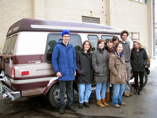 Students pose for the photo in front of a van