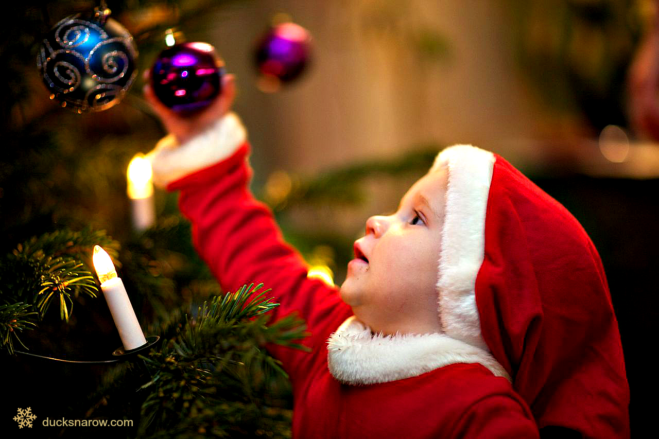 Child decorating Christmas tree; baby santa