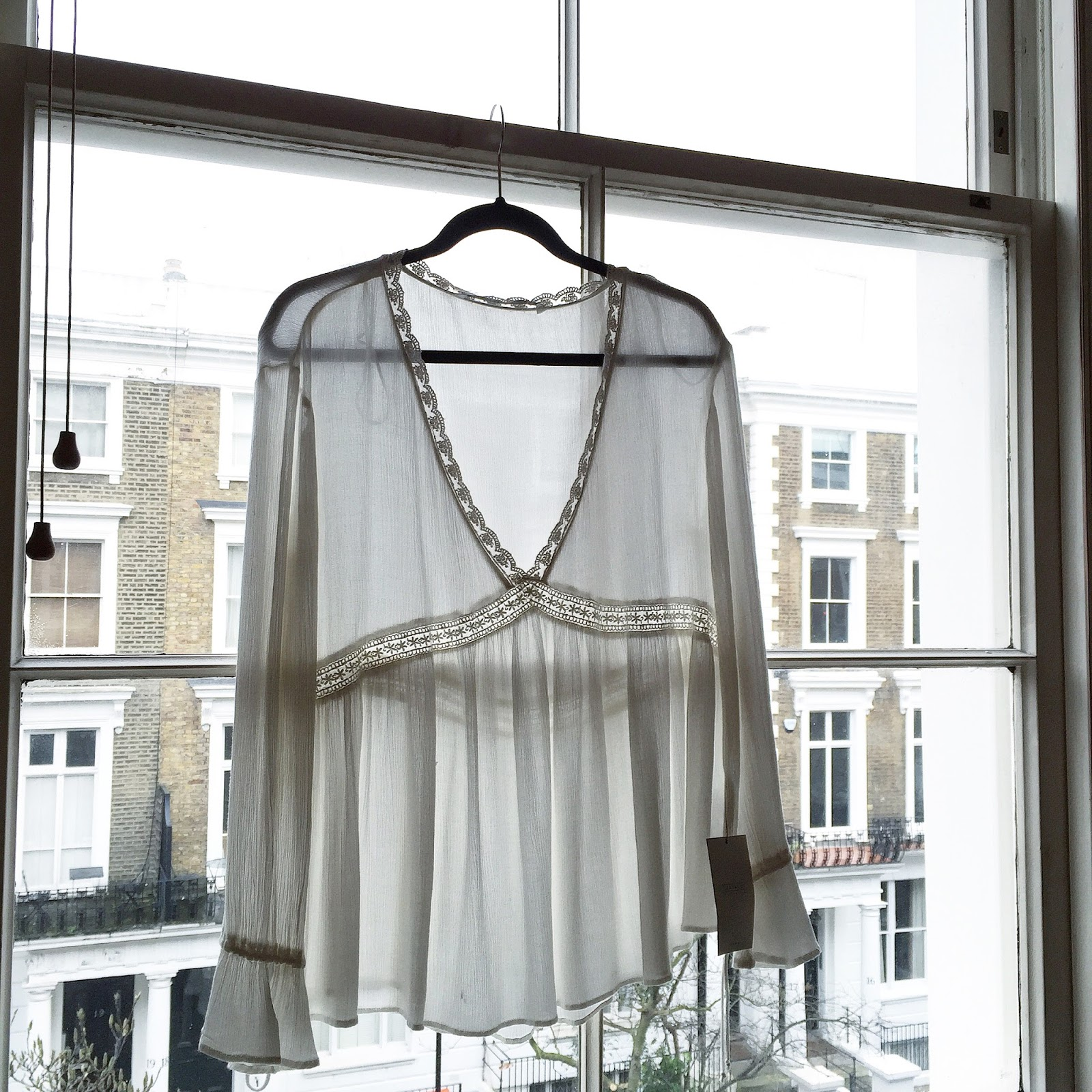 a cream coloured boho style blouse from Zara sitting on a window sill on London