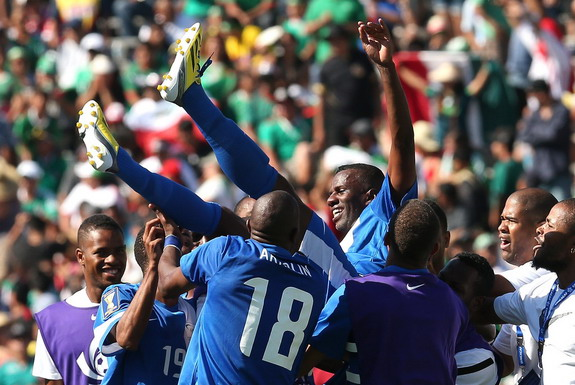Martinique player Fabrice Reuperné is lifted by his teammates after the victory against Canada