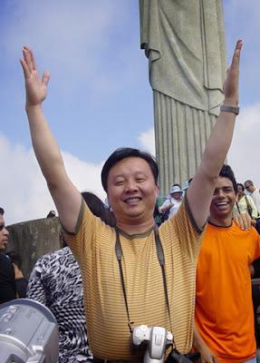 Foto de quando eu visitei o Cristo Redentor, na imagem um turista japonês abre os braços para cima, e não para os lados, como a estátua. Atrás dele aparece eu, rindo dele.