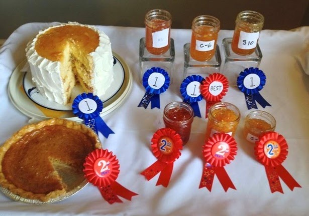 Various marmalades and cake is laid out on a table with awards.