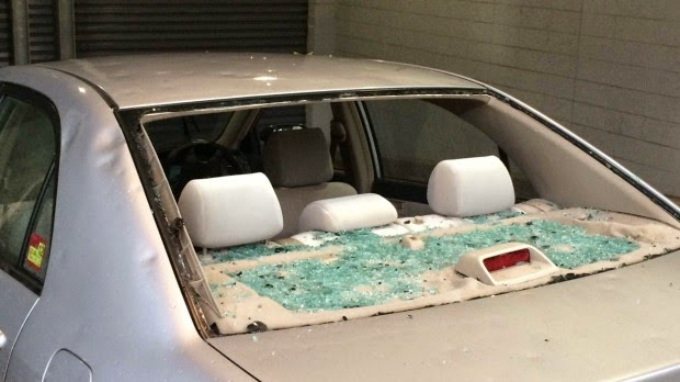 photo of back window all smashed in beige coloured saloon car and dents from hail damage to the body of the car