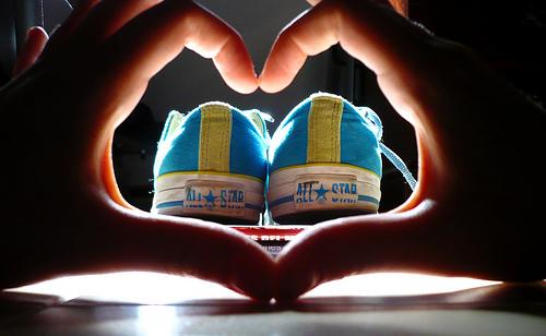 zapatillas y mano haciendo corazon