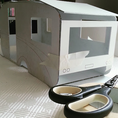 Modern dolls' house miniature retro caravan kit, undercoated and taped together with masking tape.