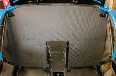 Carbon rear bulkhead fitted, siliconed, and riveted into place