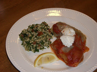 Completed cabbage rolls served with sour cream and a slice of lemon
