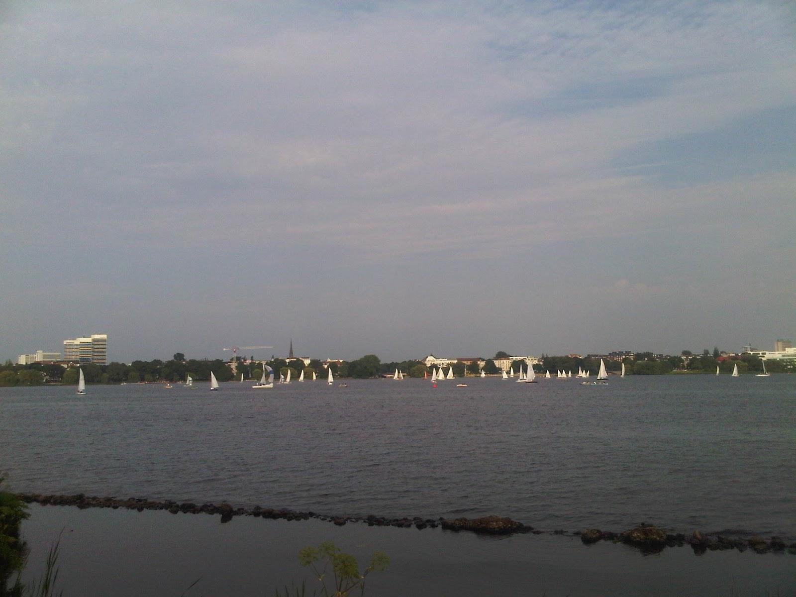 Außenalster mit Segelschiffen, Wasser, Himmel mit Wolken, Mundsburgtowers im Hintergrund.