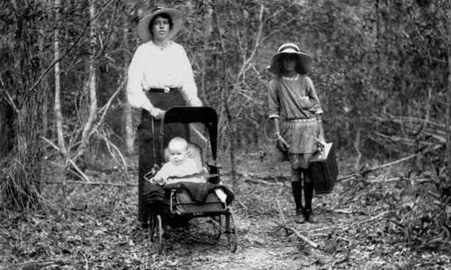Mother and children walking in bush 1910-1920