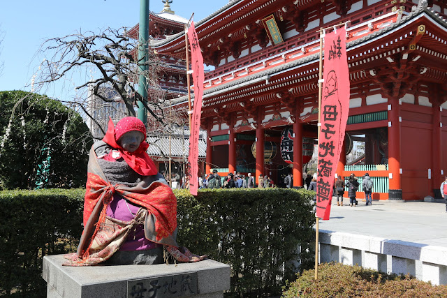 The beautiful view of a statue which is wrapped with a red cloth in front of Hozomon Gate of the main temple's hall at Asakusa Sensoji Temple in Tokyo, Japan